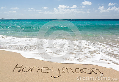 Honeymoon written in sand with sea surf