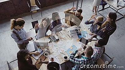Hoogste mening van creatief commercieel team die op modern kantoor werken Collega's spreken, die hoog vijf met elkaar glimlachen stock videobeelden