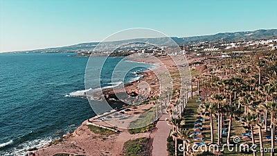 Hoogste mening van rotsachtige kust van koraalbaai in Cyprus met palmen, hotels en toevluchtgebied Sterke overzeese golven die ro stock videobeelden