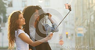 Horizontaal zijaanzicht van de mooie glimlachende multi-etnische meisjes die foto's nemen die de selfiestok in de straat gebruike stock videobeelden