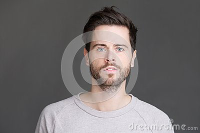 Horizontal portrait of a young man with beard looking at camera