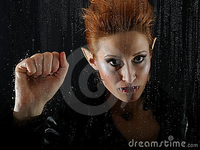 Horrible vampire woman behind rainy window