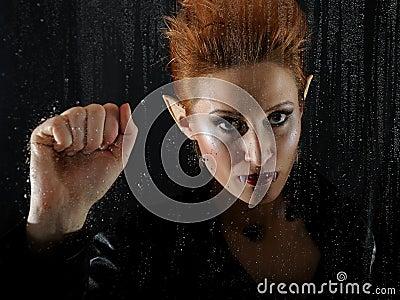Horrible vampire woman behind rainy window