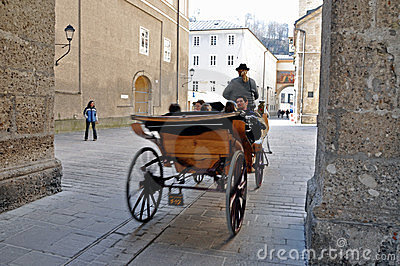 Horse driven carriage with tourists in Salzburg Editorial Stock Image