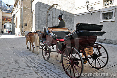 Horse driven carriage with tourists in Salzburg Editorial Image