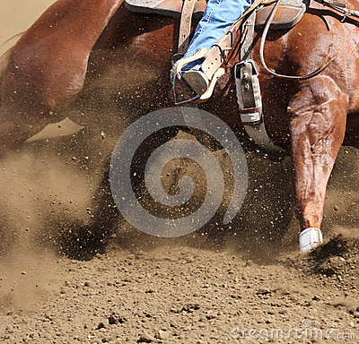 A horse and rider moving fast with dirt flying.