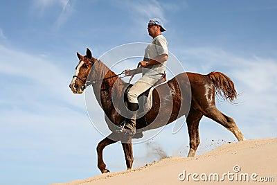 Horse rider on sand dune