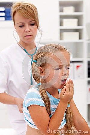 Hostande liten flicka på vård- checkup