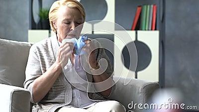 Hostande och hållande huvud för sjuk äldre kvinna på bakgrund av medicindrogen i kopp av vatten arkivfilmer