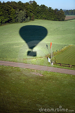 Hot air balloon shadow on field.