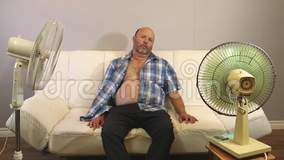 Hot and Bothered Summer. A middle aged man suffering in the heat of summer with old fashioned fans and no proper air conditioning stock footage