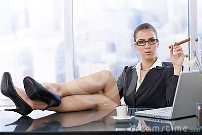Hot businesswoman with feet on desk