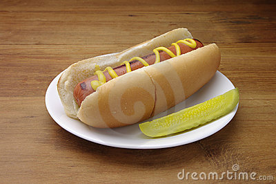 Hot dog on a white plate. Served with pickle slice