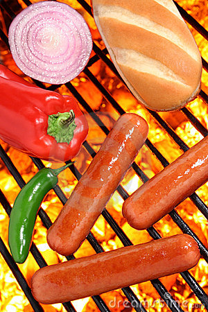 Hot dogs, bun and veggies on a barbecue grill