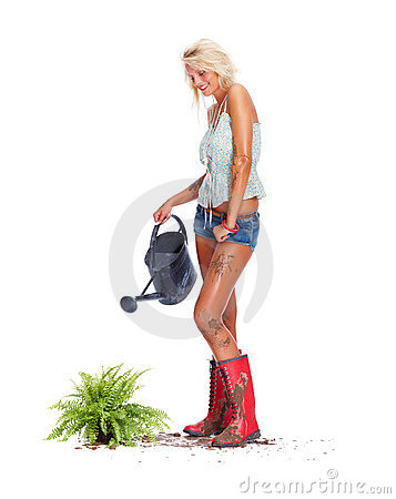 Hot young female watering a plant on white