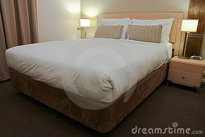 Hotel bedroom with bed and side lamps