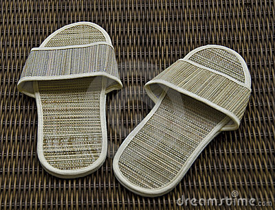 Hotel room slippers on rattan background