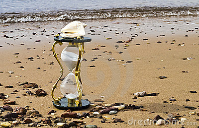 Hourglass on sandy background