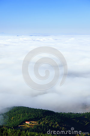 House on a hill with sea of clouds Stock Photo