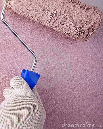 House painter using paint roller, painting wall