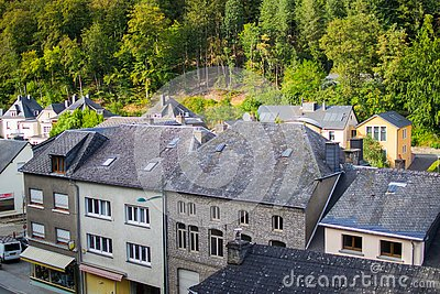 Houses in a row in a street in Clervaux, Luxembourg, with a forest at the background Stock Photo