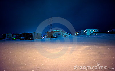 Houses on snowy hill at night
