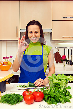 Housewife in blue apron showing ok sign