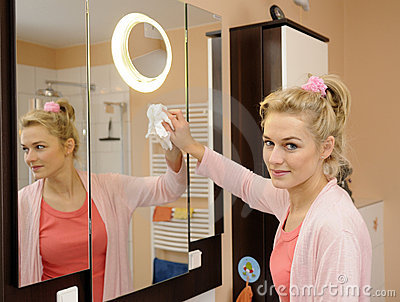 Housewife cleans a mirror