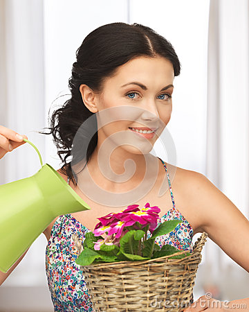 Housewife with flower in basket and watering can