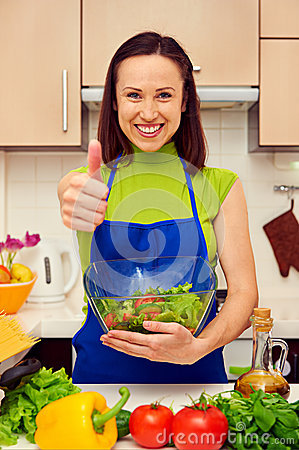 Housewife holding bowl of fresh salad and showing thumbs up