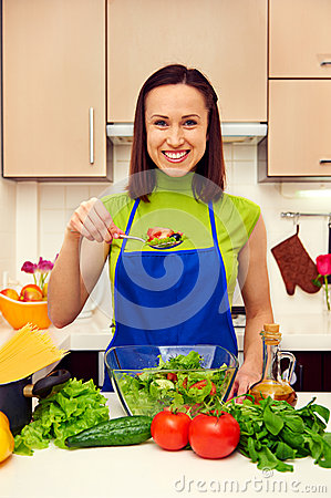 Housewife holding spoon with salad