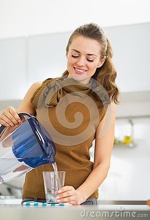 Free Housewife Pouring Water Into Glass From Water Filter Pitcher Royalty Free Stock Photography - 32838667