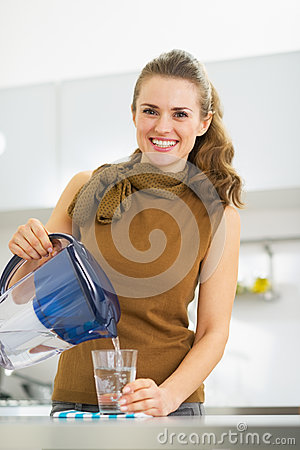 Free Housewife Pouring Water Into Glass From Water Filter Pitcher Stock Images - 32838674