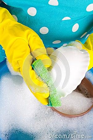 Housewife washing dishes in wash-basin
