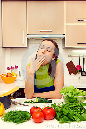 Housewife yawning in the kitchen