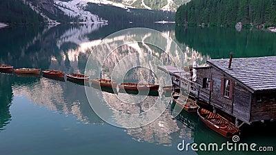 Houten boten en huizen op de zomerochtend in Lago di Braies, Italië stock video