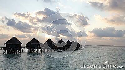 Houten weg van het eiland aan een hut over water op een zonsondergang maldives stock video