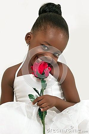 Härlig liten flicka med den röda rosen
