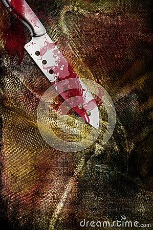 Huge bloody steel knife on filthy bloody clothing