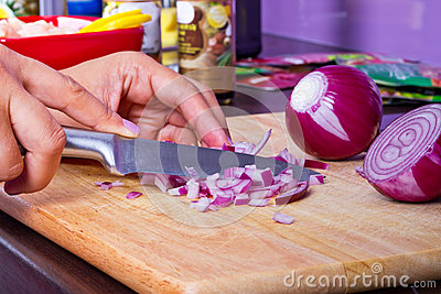 Hugga av röd lök i kök