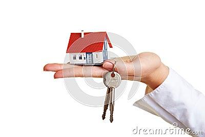 Huis en sleutels op palm van hand