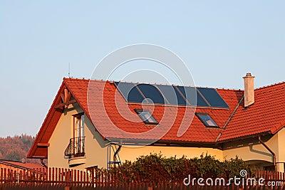 Huis met zonnepanelen op het dak voor water het verwarmen