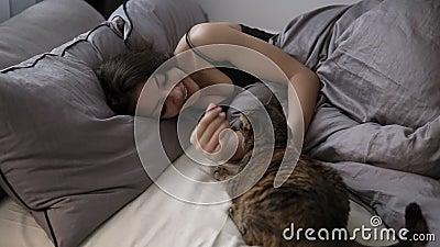 Huisdieren, comfort, rust en mensenconcept - gelukkige jonge vrouw met kat die in bed thuis liggen Donkerbruin meisje ontspannen  stock footage