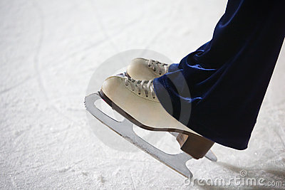 Human feet in fads standing on ice