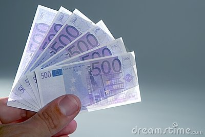 Human fingers holding little euro notes currency