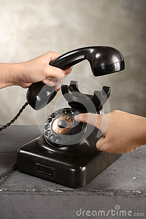 Human hand dialing numbers on antique telephone