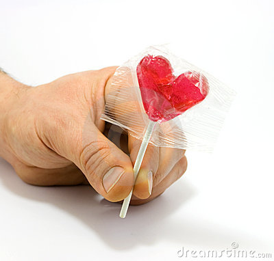 Human hand holding heart shaped candy