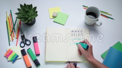 Human hand writing steps to increase sales stock video footage
