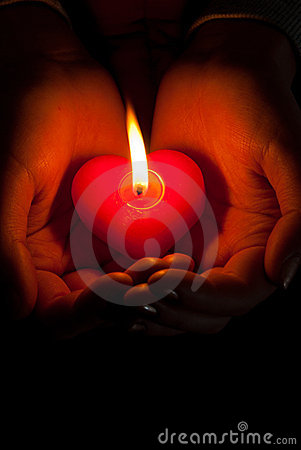 Human hands hold heart shaped burning candle