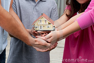 Human hands holding a model of house